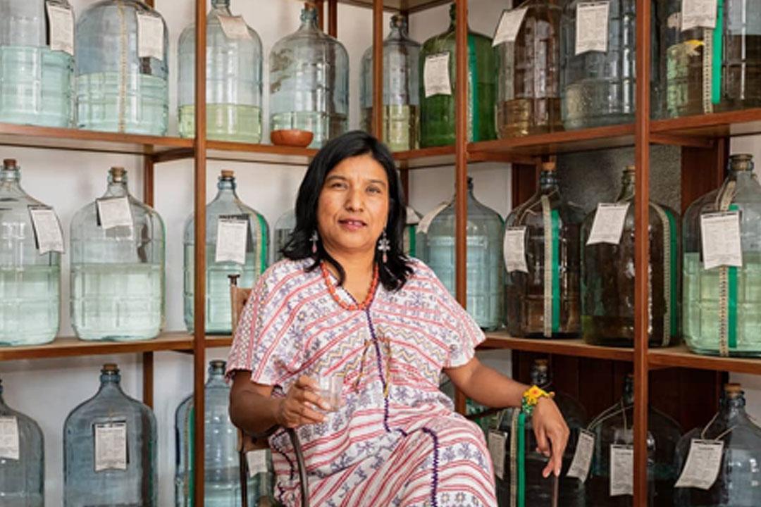image of Maestra Sosima Olivera of FaneKantsini Mezcal sitting in front of Mezcal bottles